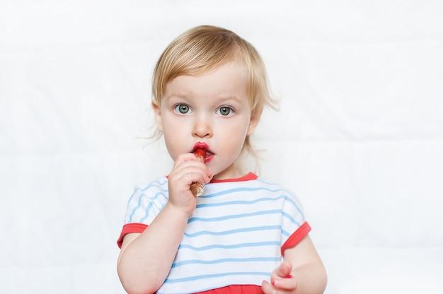 Petite fille blonde drôle maquillage lèvres avec rouge à lèvres de maman. apprendre à être une femme.