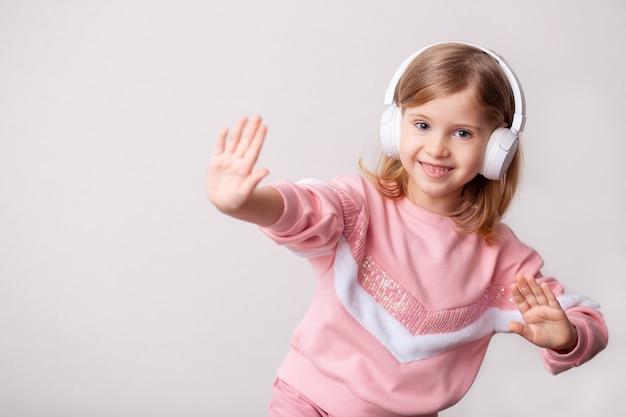 Une petite fille blonde écoute de la musique avec des écouteurs