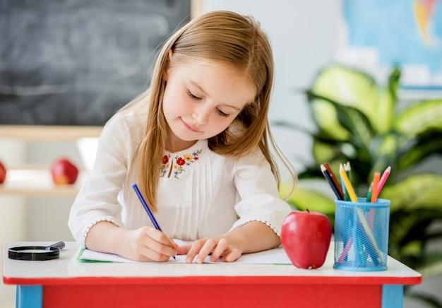 Petite fille blonde écrit le travail en classe dans la salle de classe