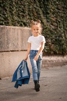 Une petite fille blonde élégante en jeans et un t-shirt blanc marche dans la rue. fille 7 ans petit modèle, bel enfant