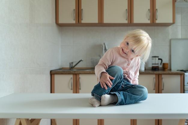 Petite fille blonde est assise dans la cuisine et sourit sournoisement.