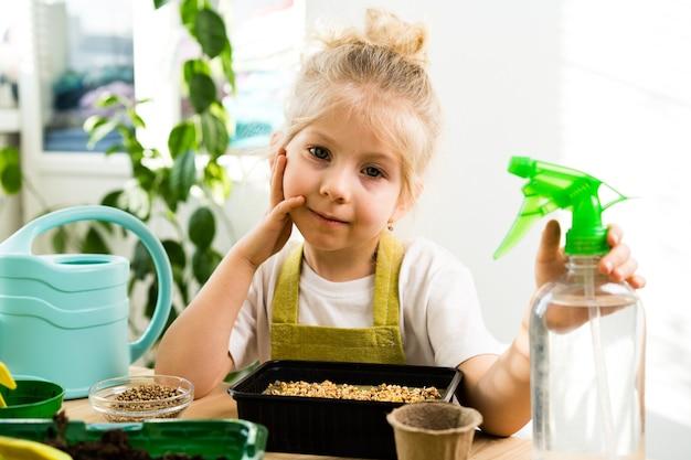 Une petite fille blonde est assise à ruminer à une table en bois avec sa joue appuyée sur sa main, faisant pousser des micro-verts, arrosant et pulvérisant avec de l'eau d'un pulvérisateur.