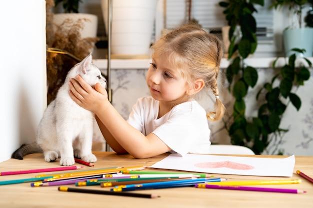 Une petite fille blonde est assise à la table et embrasse doucement un chaton écossais blanc et des sourires colorés