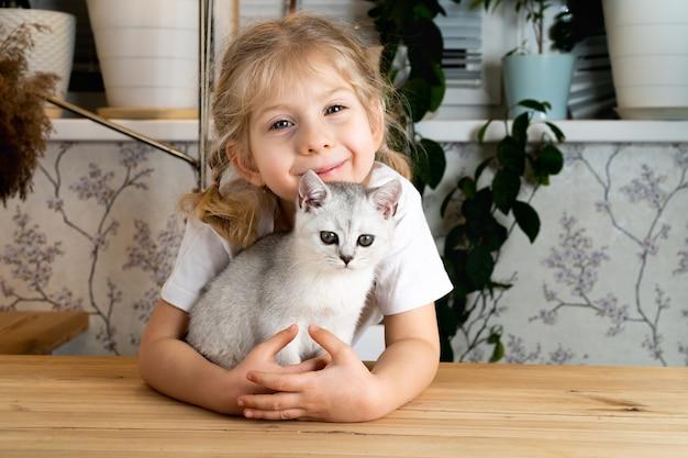 Une Petite Fille Blonde Est Assise à La Table Et Embrasse Doucement Un Chaton écossais Blanc Et Sourit Photo Premium