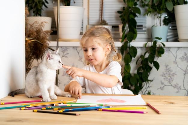 Une petite fille blonde est assise à une table et enseigne un chaton écossais blanc, des crayons de couleur et un