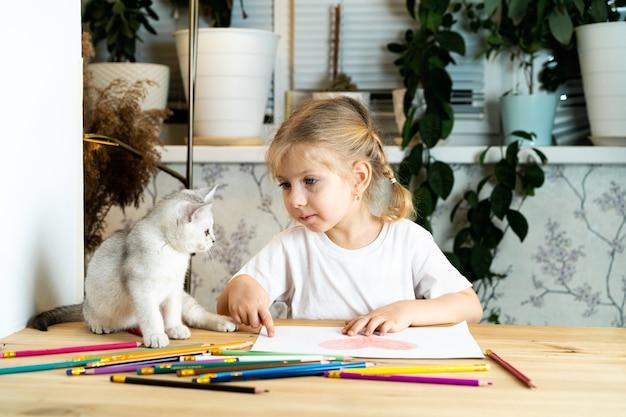 Une petite fille blonde est assise à une table et enseigne à un chaton écossais blanc des crayons de couleur et un