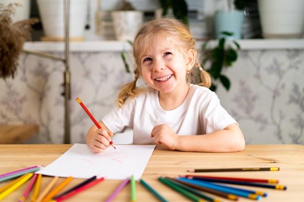 Une petite fille blonde est assise à la table, souriant et dessinant avec un crayon rouge, là