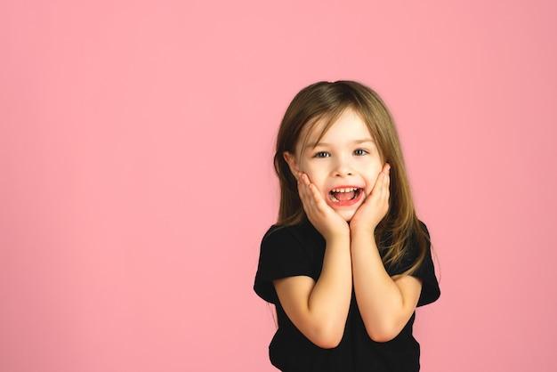 Petite fille blonde est très surprise et regarde la caméra en studio