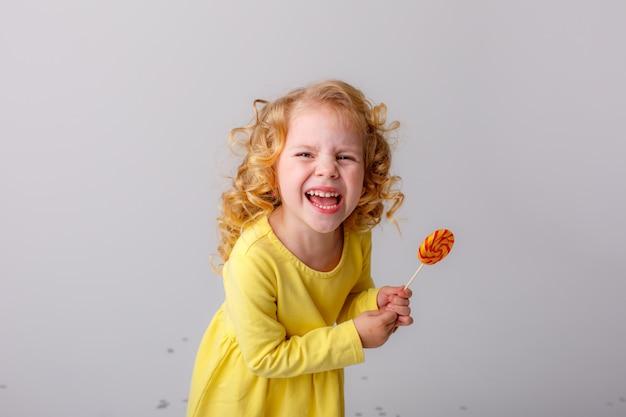 Petite fille blonde frisée lèche une sucette sur un espace blanc