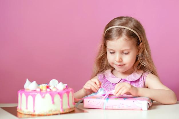 Une petite fille blonde avec un gâteau rose avec des bougies