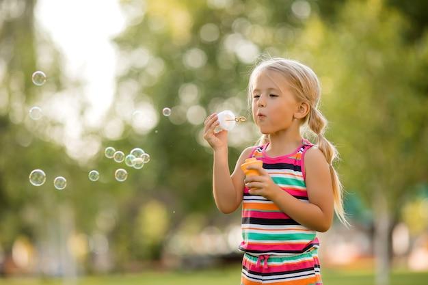 Petite fille blonde gonfle des bulles de savon en été sur une promenade
