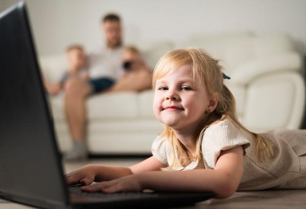 Petite fille blonde jouant sur un ordinateur portable