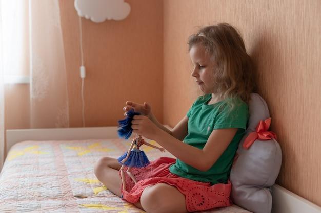 Petite fille blonde jouant avec la poupée dans le concept d'enfance de chambre à coucher