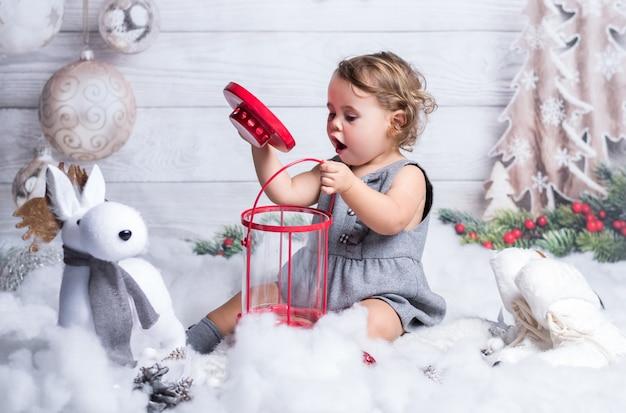 Petite fille blonde joue dans la décoration d'hiver de noël.