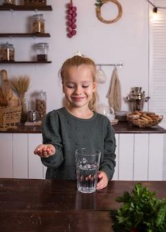 Une petite fille blonde joyeuse dans un pull vert est assise à une table et boit de l'eau avec des vitamines