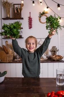 Une petite fille blonde joyeuse dans un pull vert est assise à une table et tient des bouquets de persil