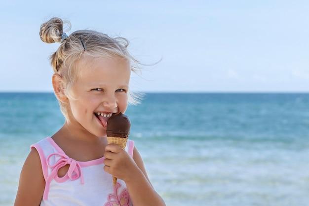 Petite fille blonde lèche la glace au chocolat et sourit sur fond de mer et de ciel