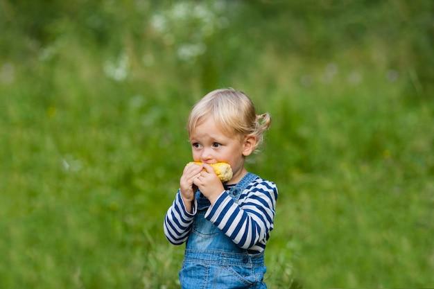 La petite fille blonde mange du maïs au camping