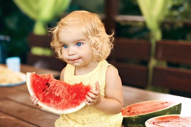 Petite fille blonde mange une pastèque juteuse dans le jardin. les enfants mangent des fruits dans la rue. une alimentation saine pour les enfants. jardinage pour tout-petits.