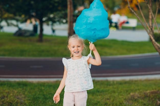 Petite fille blonde mangeant de la barbe à papa bleue dans le parc.
