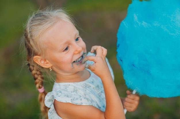 Petite fille blonde mangeant la barbe à papa bleue en parc