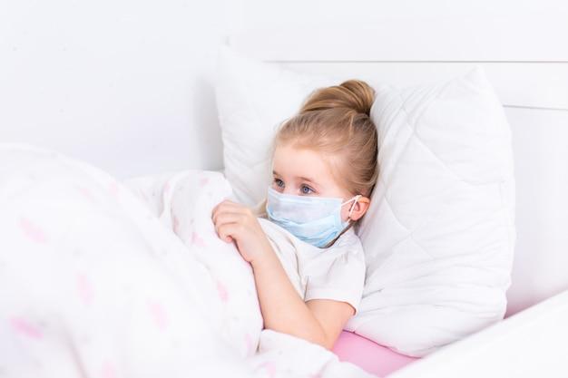 Petite fille blonde en masque de protection médical couché dans un lit blanc dans une salle blanche.