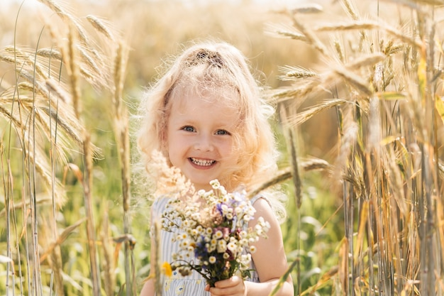 Petite fille blonde mignonne avec un bouquet des fleurs sauvages en nature pendant l'été