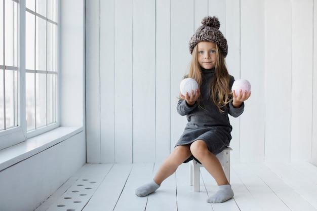 Petite fille blonde offrant des boules de neige