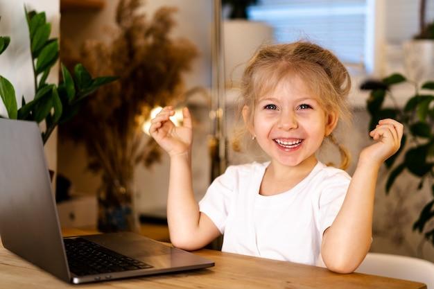 Petite fille blonde avec un ordinateur portable est assis à une table et sourit