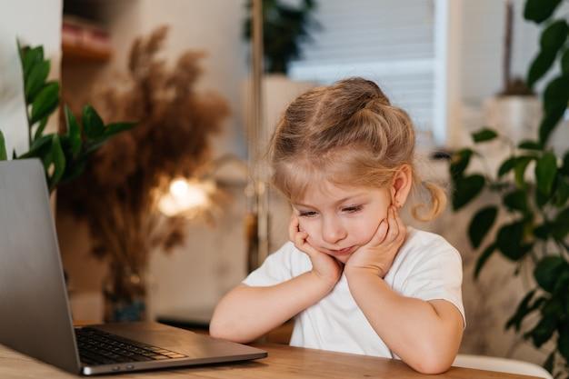 Petite fille blonde pensive assise devant un ordinateur portable avec un visage triste