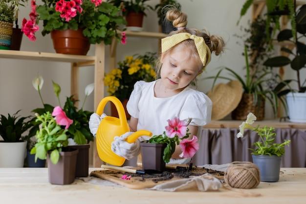 Petite fille blonde plantes et greffes et arrose les fleurs d'intérieur petite aide par les tâches ménagères