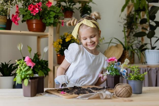 Petite fille blonde plantes et greffes eaux fleurs d'intérieur petite aide aux tâches ménagères