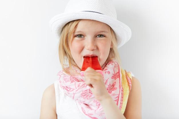 Petite fille blonde portant un chapeau blanc et manger de la crème glacée