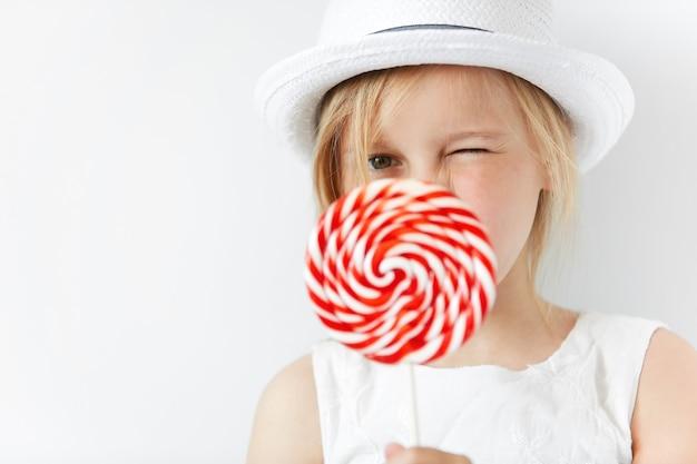 Petite fille blonde portant un chapeau blanc et tenant des bonbons au sucre