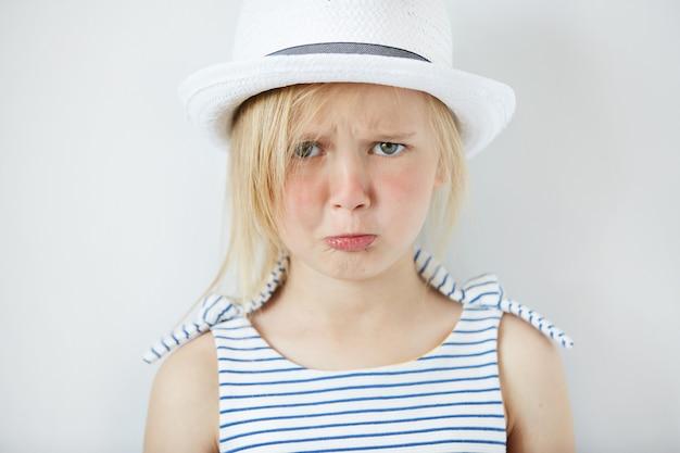Petite fille blonde portant un chapeau blanc