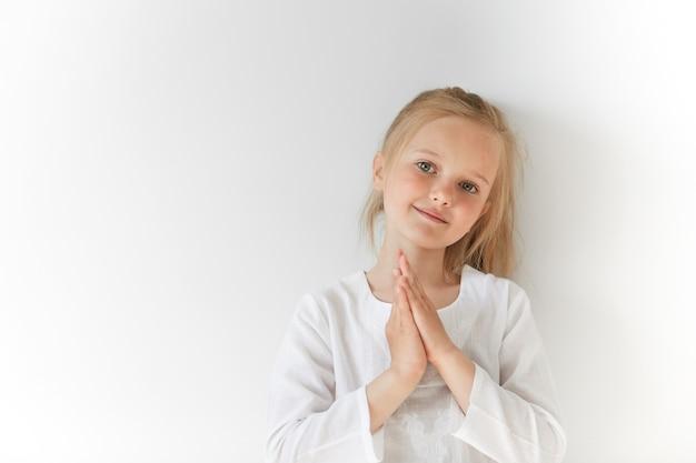 Petite fille blonde portant un chemisier blanc