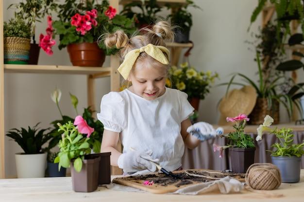 Petite fille blonde portant des gants de travail plantes et greffes et eaux fleurs d'intérieur