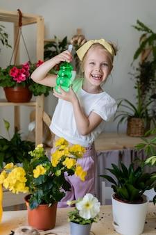 Petite fille blonde portant des gants de travail pulvérise un distributeur de balles ou arrose des fleurs d'intérieur