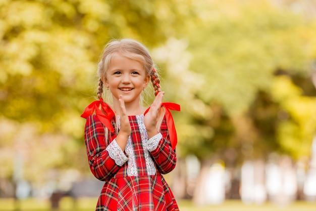 Petite fille blonde première niveleuse robe à carreaux rouge souriant dans la rue
