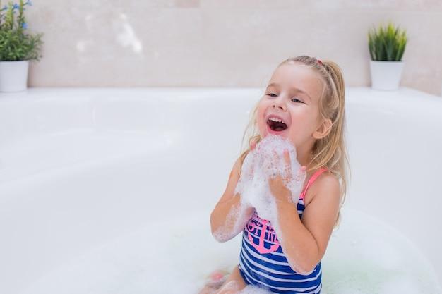 Petite fille blonde prenant un bain moussant dans une belle salle de bain. hygiène des enfants. shampooing, traitement capillaire et savon pour enfants. kid se baignant dans une grande baignoire.