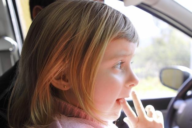 Petite fille blonde profil voiture véhicule intérieur portrait