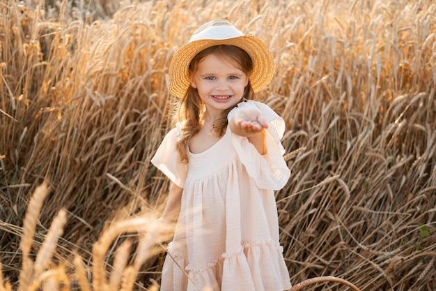 Petite fille blonde en robe de mousseline beige tient des grains de blé dans la paume de sa main dans un champ de blé au coucher du soleil.