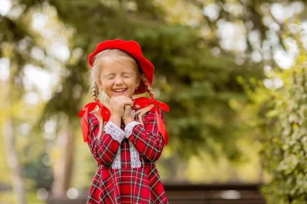 Petite fille blonde en robe rouge