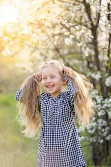 Petite fille blonde s'amusant dans le parc du printemps.