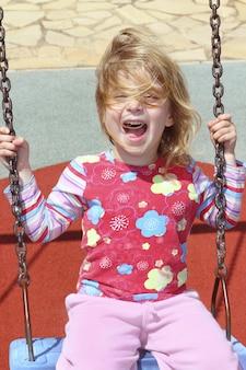 Petite fille blonde se balançant dans les cheveux en désordre du parc