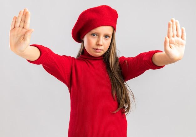 Petite fille blonde sérieuse portant un béret rouge montrant un geste d'arrêt regardant l'avant isolé sur un mur blanc