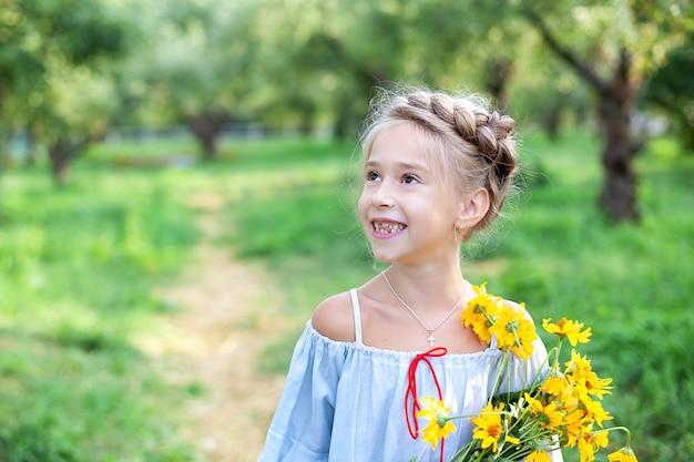 Petite fille blonde souriante avec un bouquet de fleurs jaunes enfant dans le jardin d'été