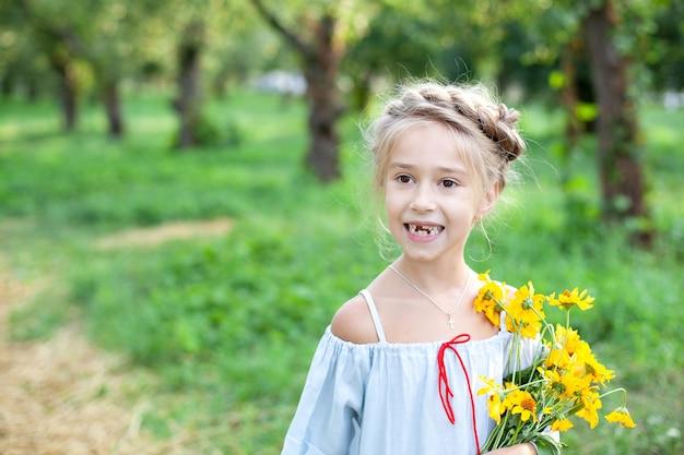 Petite fille blonde souriante avec un bouquet de fleurs jaunes sur fond de jardin