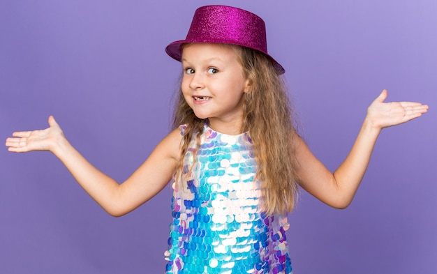 Petite fille blonde souriante avec un chapeau de fête violet tenant les mains ouvertes isolées sur un mur violet avec espace de copie
