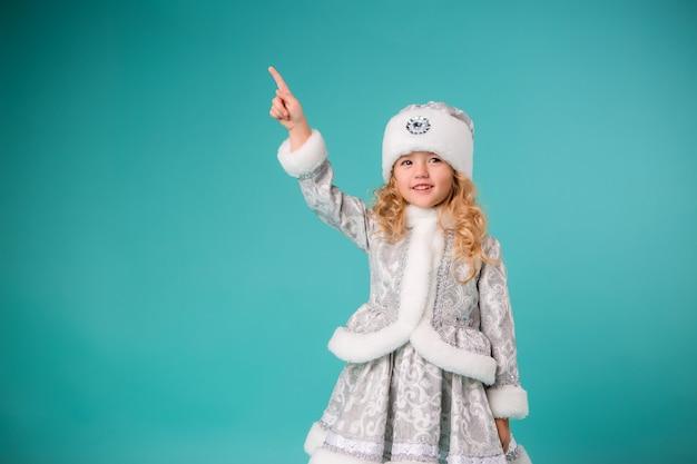 Petite fille blonde souriante en costume de fille des neiges isoler sur le mur bleu